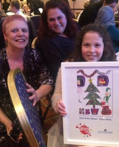 Poppy with a framed copy of her card with mum Janine (centre) and our Director Chris Whiley