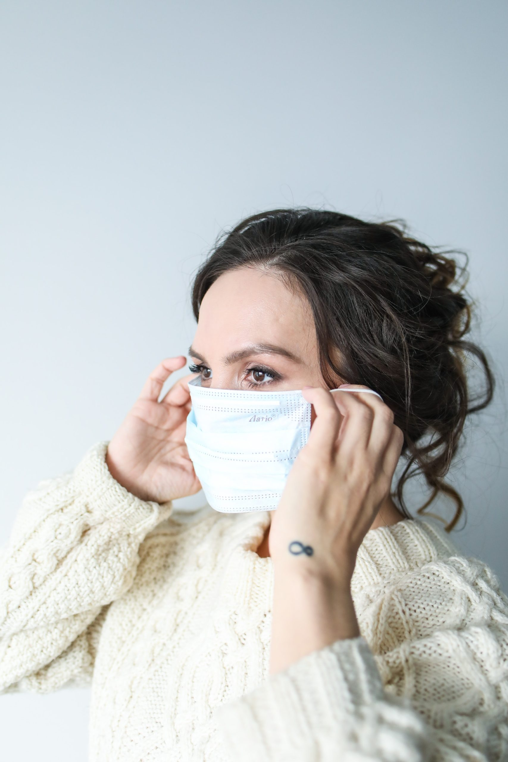 Woman adjusting a medical style face mask.